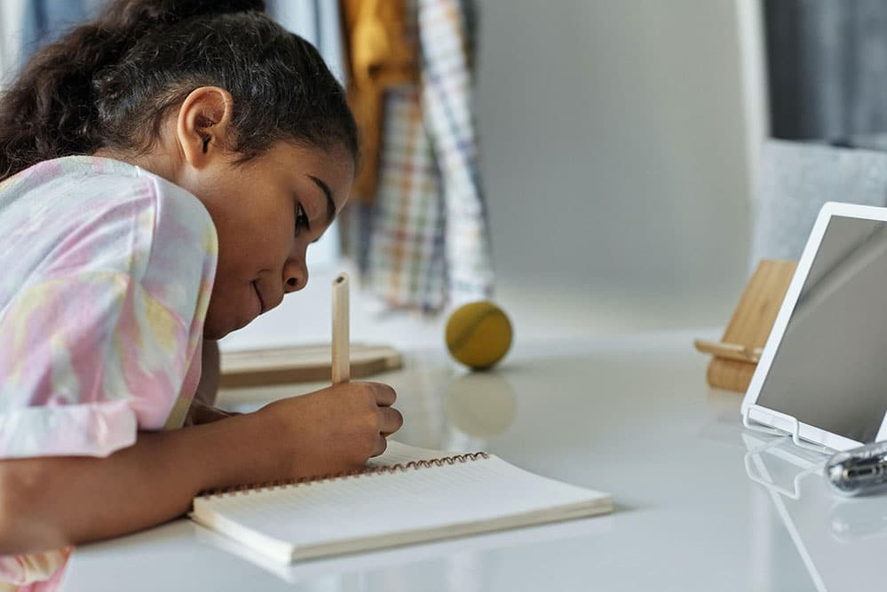 Child sitting at desk with a pencil in their hand writing in a book